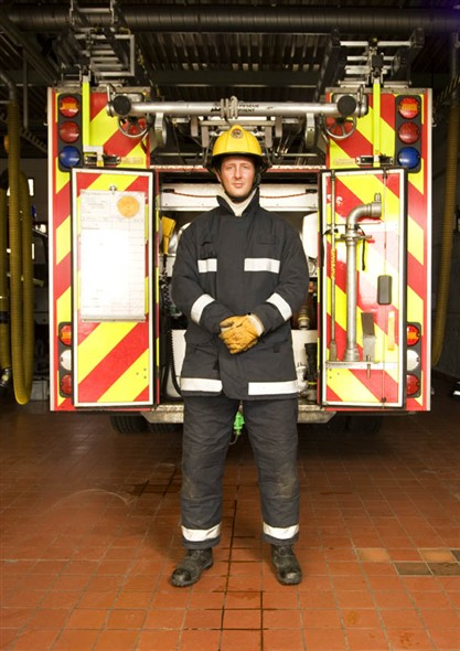 Photo:Portrait of fireman Aaron Tills infront of one of the fire engins