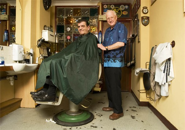 Photo:Portrait of Philip Jones, owner of PJ's cutting the hair of one of his regular customers Anthony Thomas