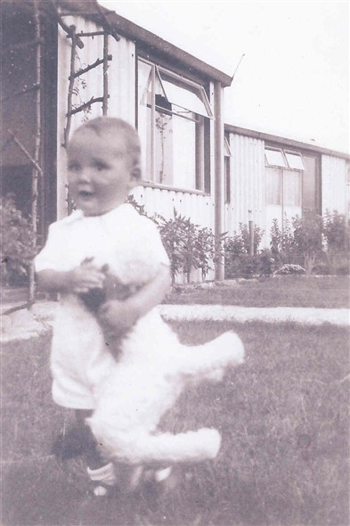 Photo:Photograph of a child outside a prefab on Shrublands Estate